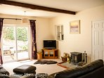 Exmoor Holidays Porlock has log burning fire in the living room, with comfortable leather furnishing