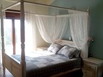 A large bedroom with a king size bed in the upper floor, Tv, air-condition and ceiling-fan.