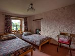 Comfortable twin bedroom with open village views