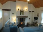 Cosy living room with vaulted ceiling and wood burner in traditional stone fireplace.