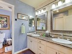 Master bathroom has double vanity and large walk in closet opposite.