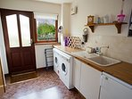 Utility room with washing machine, tumble drier and freezer.