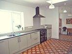 Kitchen with range cooker, integrated dishwasher, double sink and large fridge-freezer.