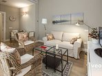 The living room is furnished with a sofa, 2 armchairs, central table and TV.