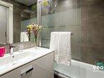 The second bathroom has bathtub with an overhead shower.
