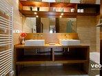 Bathroom with double washbasin, toilet and bathtub.