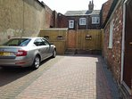 Private parking with gate leading to courtyard terraced area