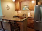 Lower level wet bar with refrigerator, dishwasher, and microwave