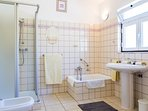 Bright and airy bathroom with small bath and separate shower cubicle.
