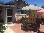 Private garden patio with umbrella table and grill.