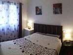Bedroom 1. Queen size bed, air conditioner.