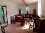 The second living room with piano and courtyard access.
