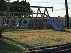 swing set in fenced in side yard