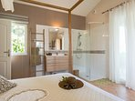 Salle de bain avec douche à l'italienne, lavabo et miroir. Un wc se trouve dans le couloir