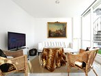 The living area is furnished with a sofa, table, 2 armchairs and TV.