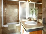 En-suite bathroom with double washbasin, bathtub and toilet (bedroom 1).