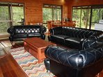 Open plan lounge featuring a fireplace,  leather chesterfield lounge and native outlook.