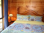 Guest queen bedroom featuring comfortable bed linen, lead light lamp and fresh towels.