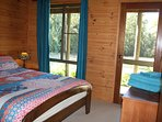 The main bedroom has a fabulous outlook, with a door onto the external deck and overlooking the dam.