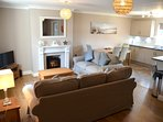 Stunning, open plan living area with comfortable sofas, gorgeous lighting and traditional fireplace