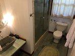 Hallway to front bedroom bathroom with river rocks shower floor,grant sink.