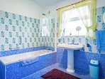 Large and airy en suite bathroom with full size bath and shower over.