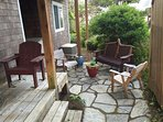 Back deck with two wood chairs and a stone patio with a beautiful wood bench and two chairs