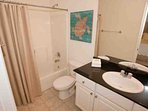 Guest bath with single vanity, tile floors and tub/shower