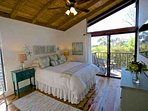 Guest bedroom with TV and balcony that wraps around the back of house