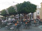 piazza del paese con locali e tavolini sulla piazza