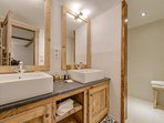The shower room features a large walk-in shower and dual sinks featuring large, well lit mirrors.