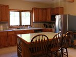 Fully stocked kitchen, stainless appliances, dishwasher, double sink, blender, large island