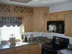 Fully equipped kitchen with electric stove, microwave and dishwasher.