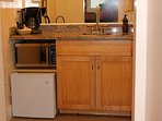 Wet bar with refrigerator, microwave, and coffee pot are convenient features.