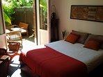 une chambre claire ensoleillée avec sortie directe sur une partie de la terrasse avec salon privatif