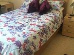 Double bed in master bedroom. Desk.