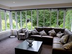 Living room with views of the loch and 2.4 acres of gardens.  Seating for 6 with satellite TV.