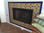 Gas fireplace in living room with mexican tile surround.