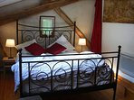 Master bedroom with large traditional French bed, beams of Oak and Beechwood.