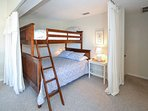 Privacy curtains surround the bunk with double bed on the lower level and a twin size on the upper