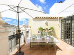 Terrace furnished with a large dining table and chairs - ideal to enjoy a meal outside.