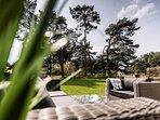 Terrasse mit Lounge-Möbeln und seitlichem Achterwasserblick über herrliche Biotopfläche