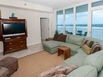 Living room with flat screen TV and views to private balcony overlooking Little Lagoon