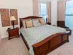 Carpeted master bedroom with king bed, sitting area and 2 nightstands with lamps