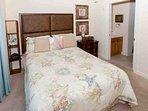 Guest bedroom with queen bed looking towards ensuite bath