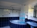 Grande salle de bains avec baignoire d'angle
