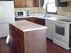 Kitchen: refrigerator, microwave, stove, dishwasher, island, drawers, cabinets