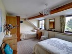 The larger bedroom on the first floor has a double bed and a single bed, and a small wall-mounted TV