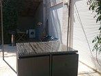 La terrasse couverte avec le lave linge, le barbecue