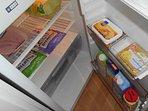 The fridge contains ham and eggs, cheese, milk, yoghurt and orange juice